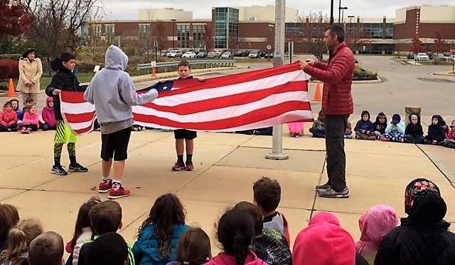 Paul McNeal and Safety Patrol members properly fold a USA flag