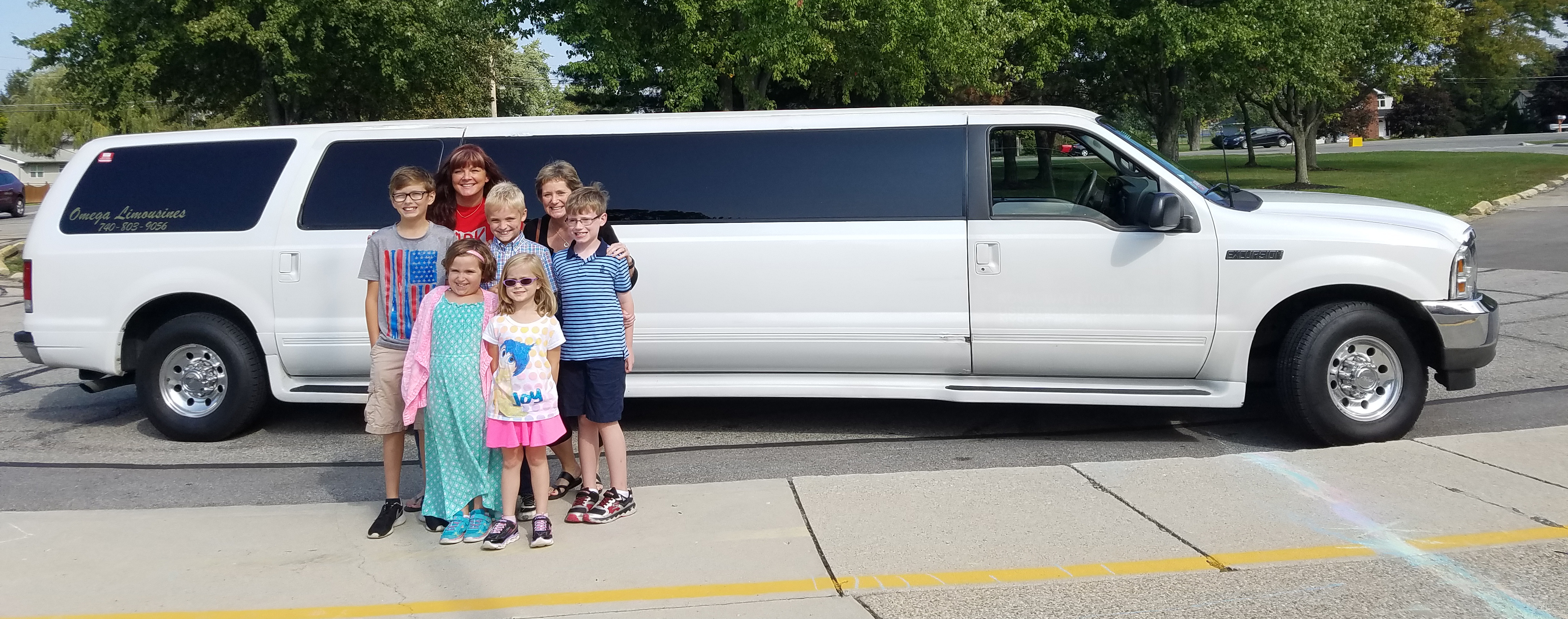 Five students, a secretary and principal stand in front of a limo before taking a ride to lunch.