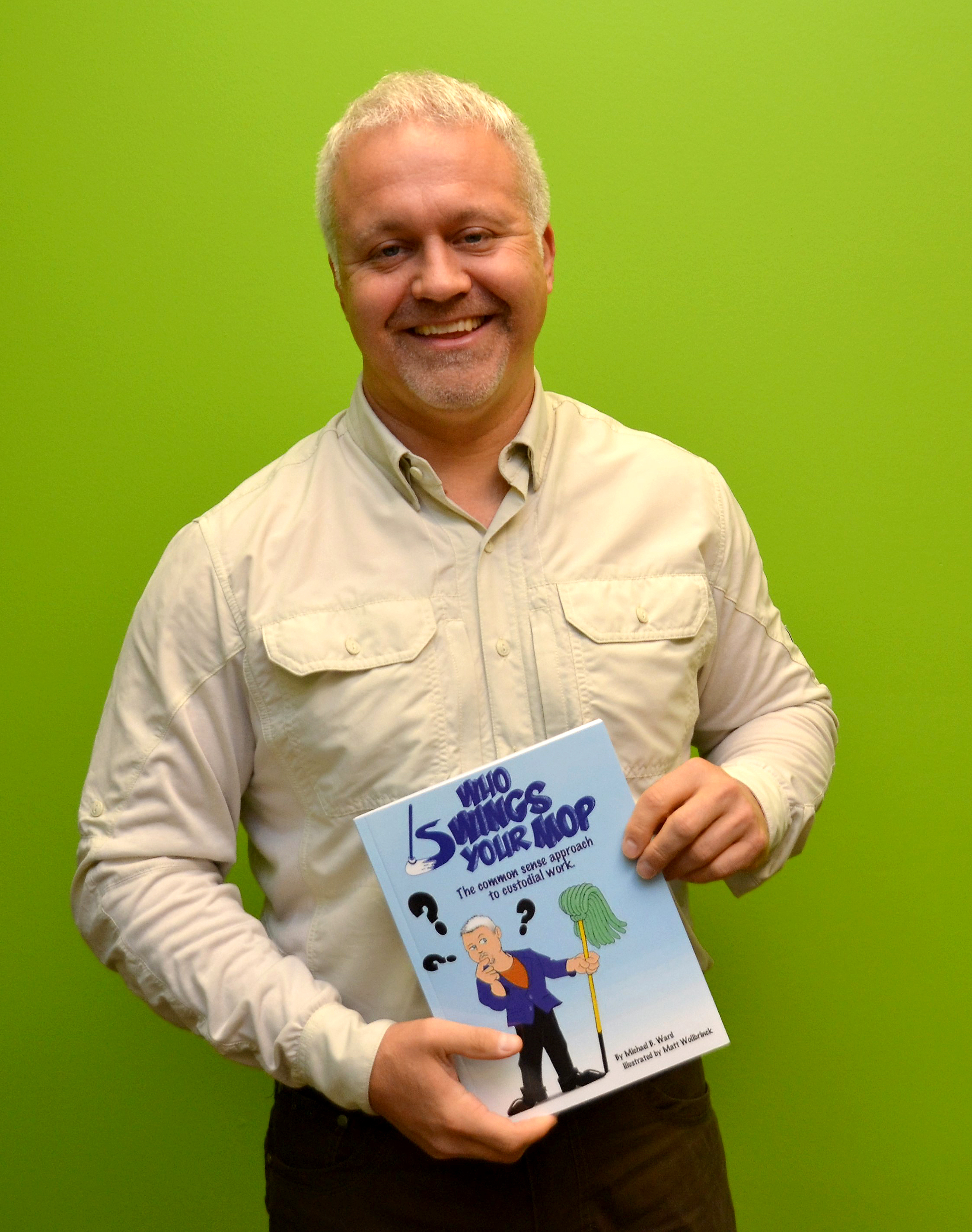 Mike Ward holds his recently published a book titled, Who Swings Your Mop?  The Common Sense Approach to Custodial Work.