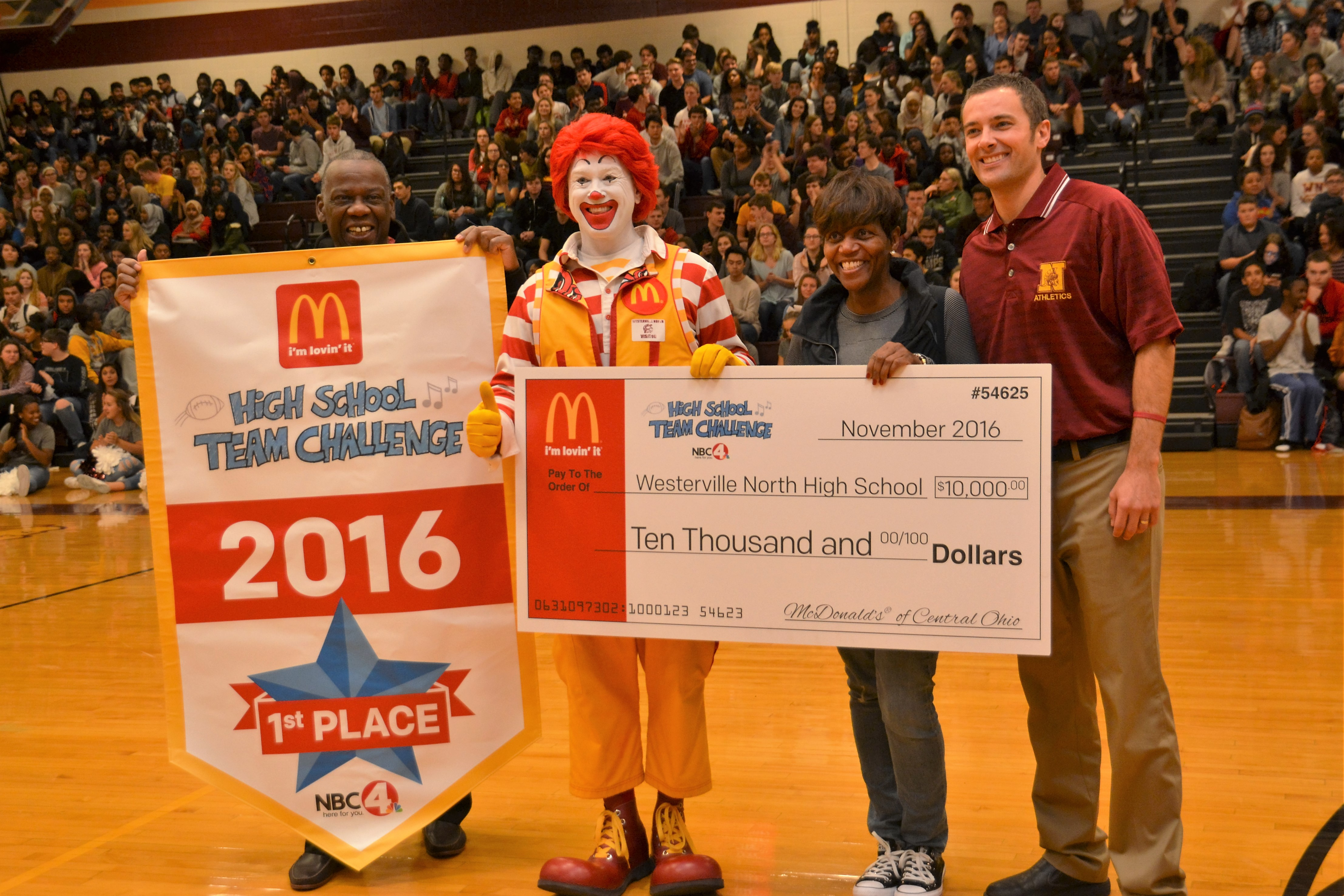 Local McDonald's owner/operators Myron and Linda Ware, along with Ronald McDonald and Westerville North Athletic Director Wes Elifritz are pictured with a $10,000 check.