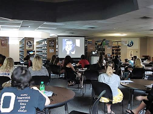 Students in the school library watching each other's films.