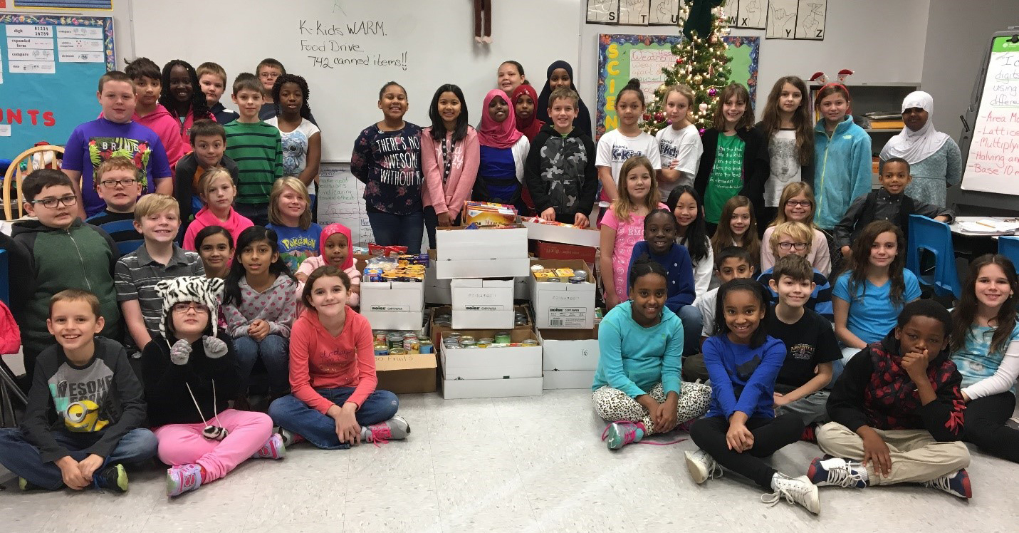 Wilder K-KIDS students sit with their collected cans of food