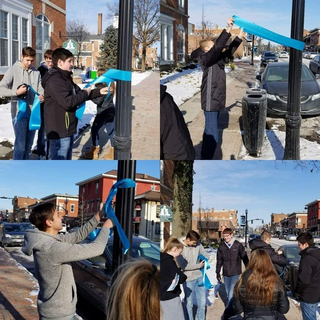 Students tying blue ribbons for Central Cervical Cancer awareness