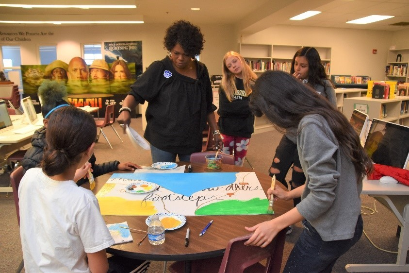 Mentor Davia Stevenson works with her group to create a board of inspiration for the Heritage Middle School community.