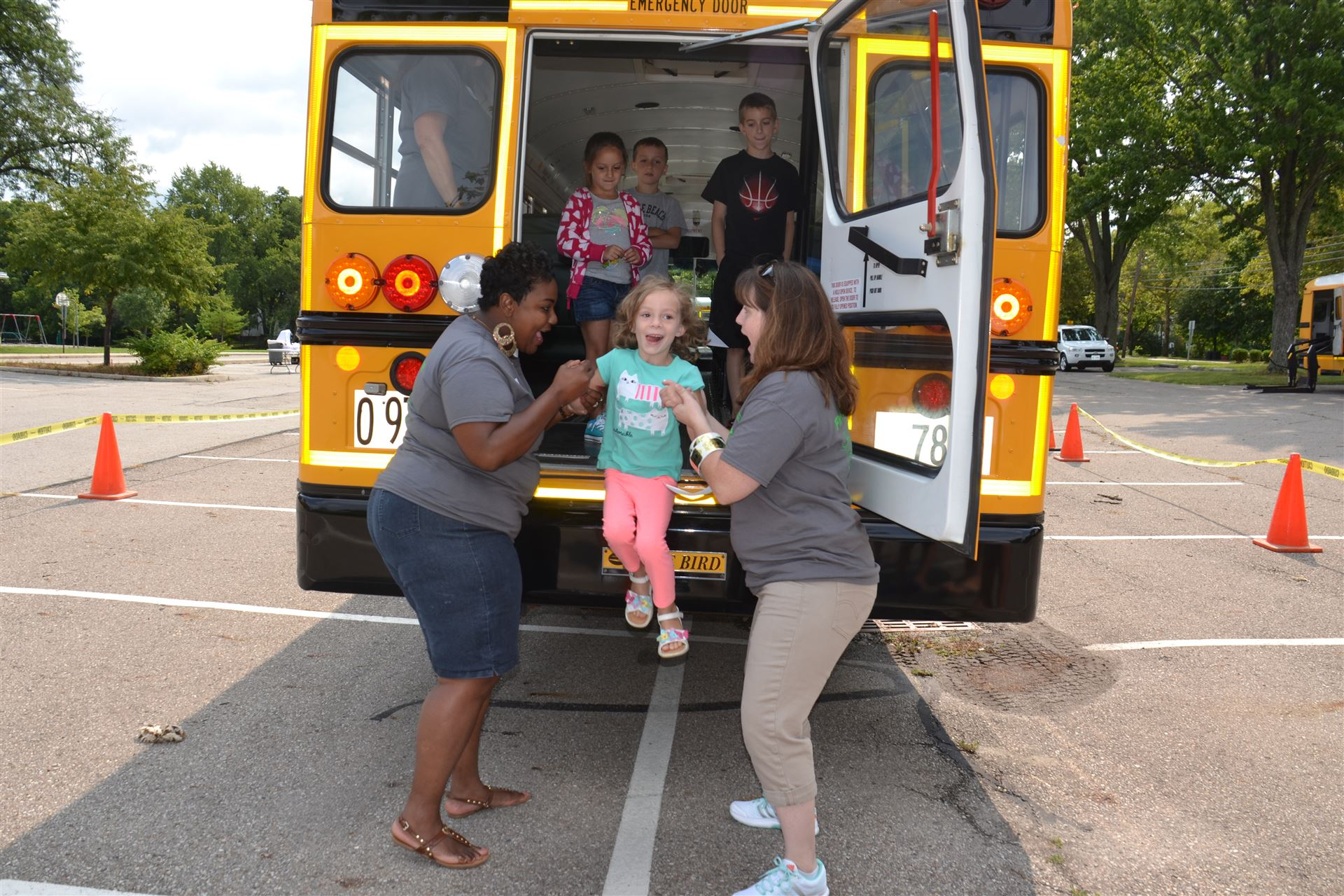 Bus drivers help students off a bus