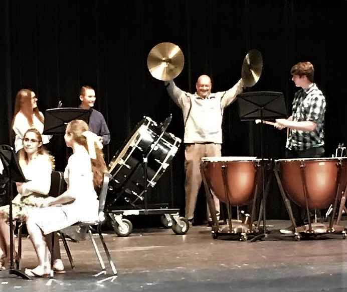 Principal Todd Spinner on stage holding cymbals while preforming with with the Westerville Central Symphonic Band.