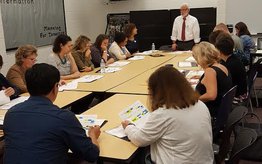 Westerville Central Assistant Principal Brad Adams talks with 15 educators sitting around a table.
