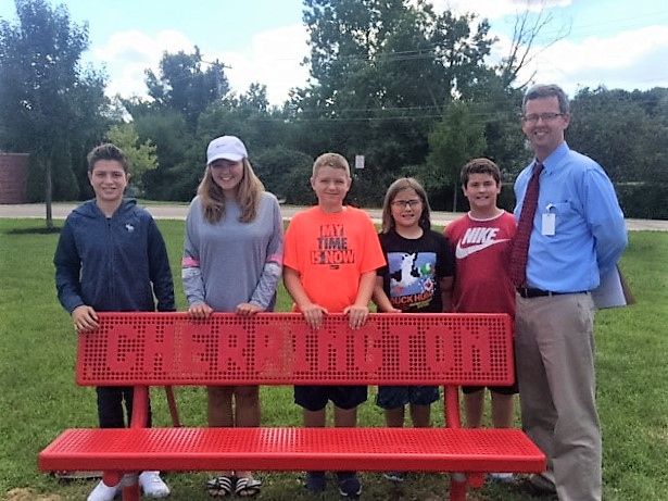Cherrington Principal Andy Heck admires the school's new bench with fifth grade students