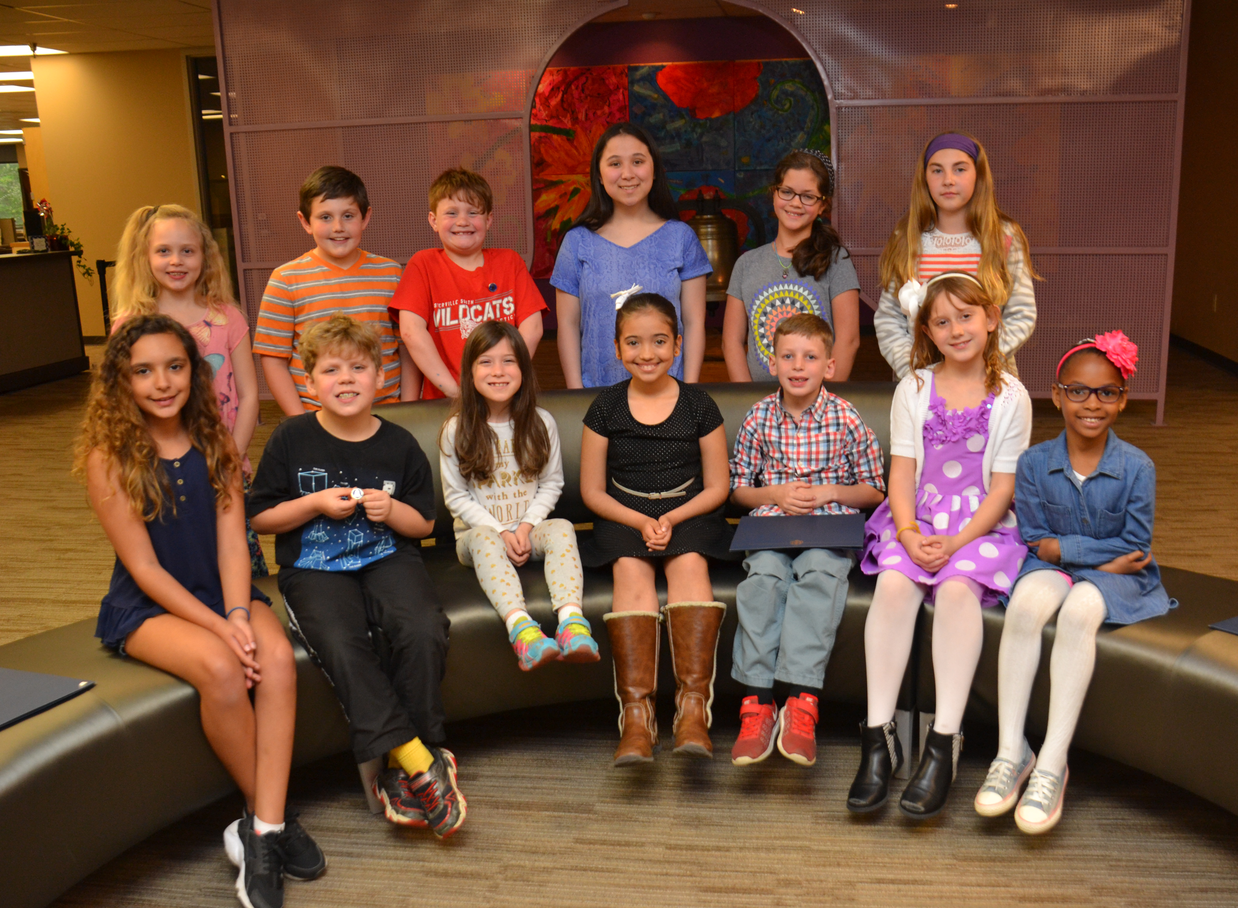 Thirteen State Reflections competition students sit on a couch after being recognized at a Board meeting.