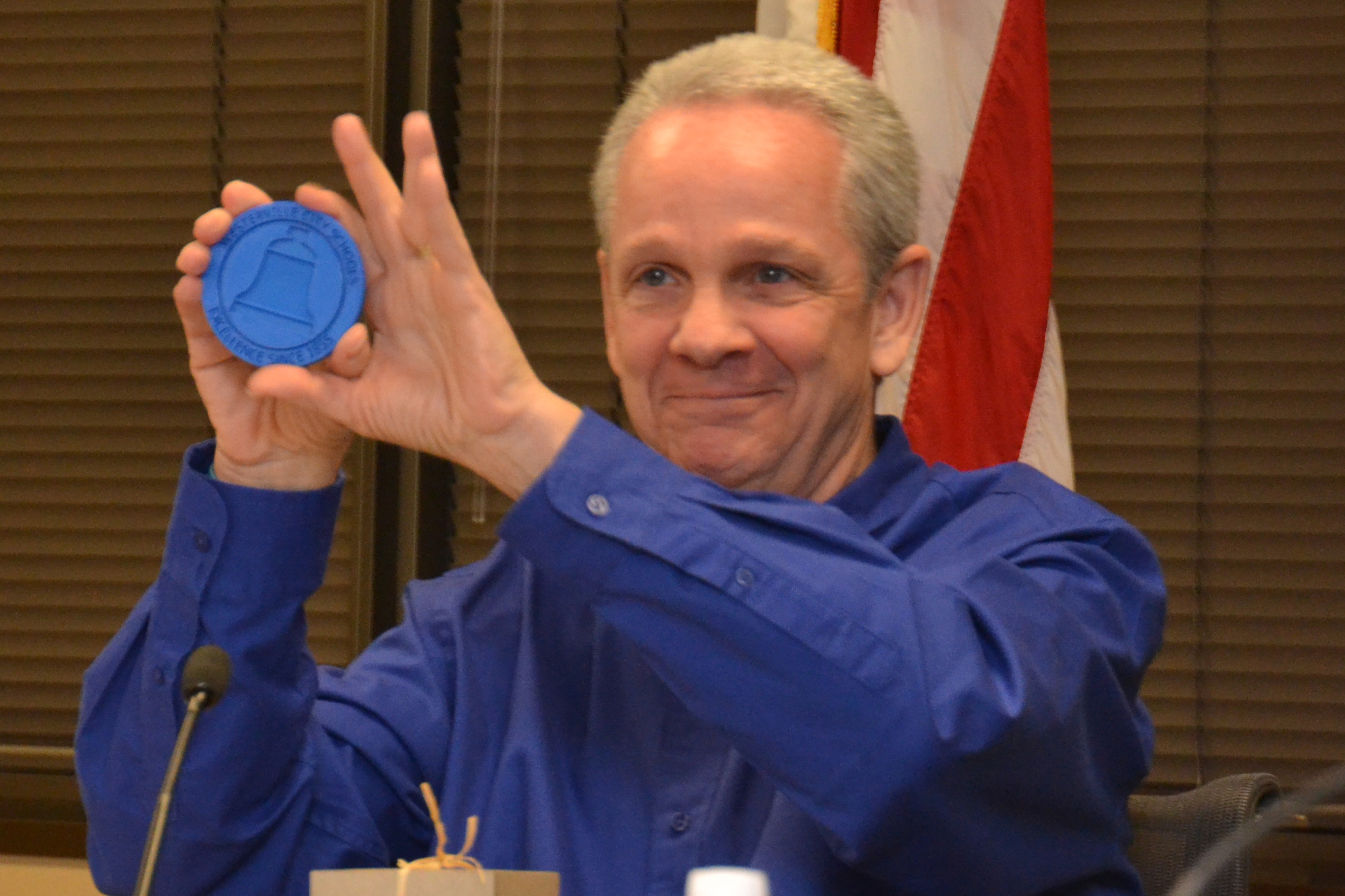 WCSD Board of Education President Rick Vilardo displays a special coaster made in the mobile FabLab