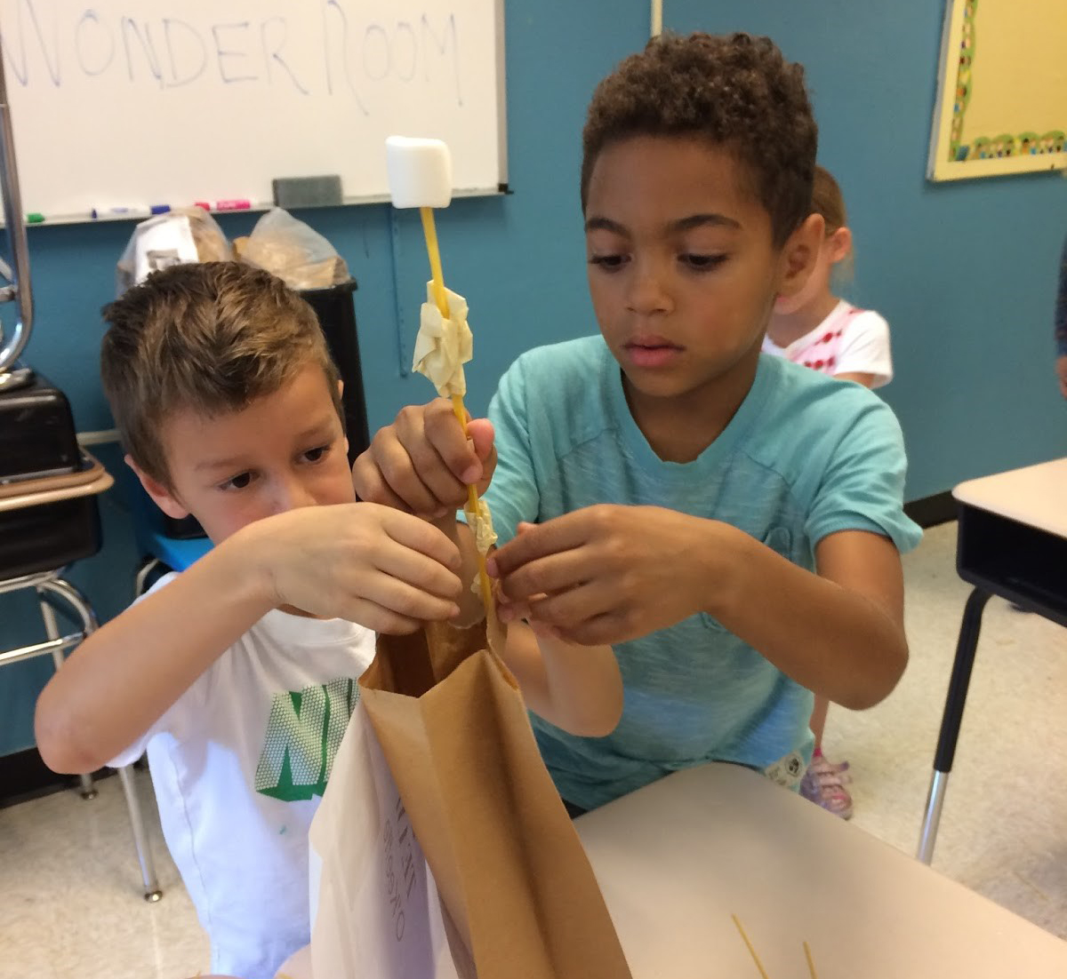 Two students work together in the Wonder Room to try and build the tallest structure using dry spaghetti, marshmallows, tap, and a brown bag