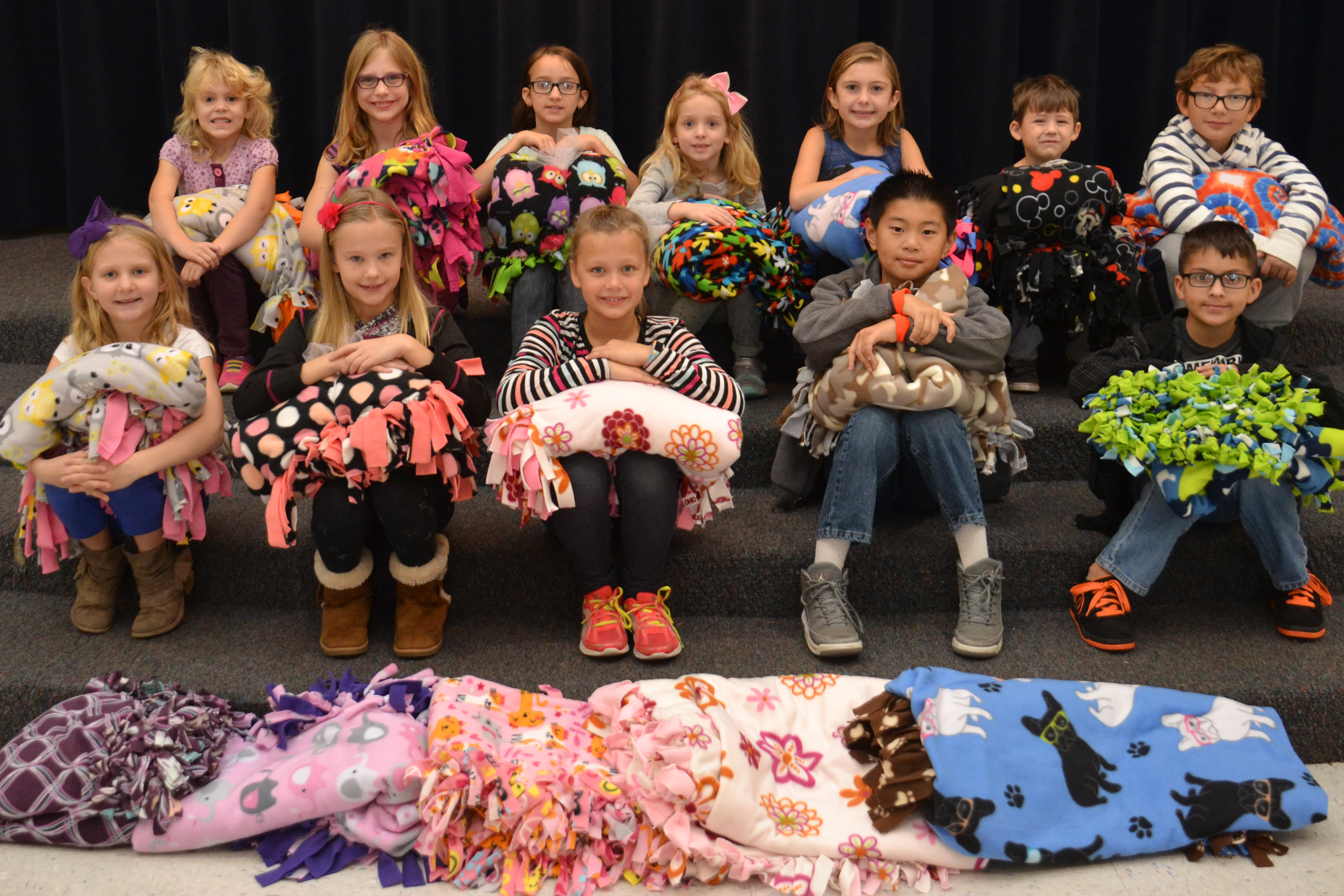 McVay Elementary students pose with some of the blankets they made to be distributed at the Ronald McDonald House.