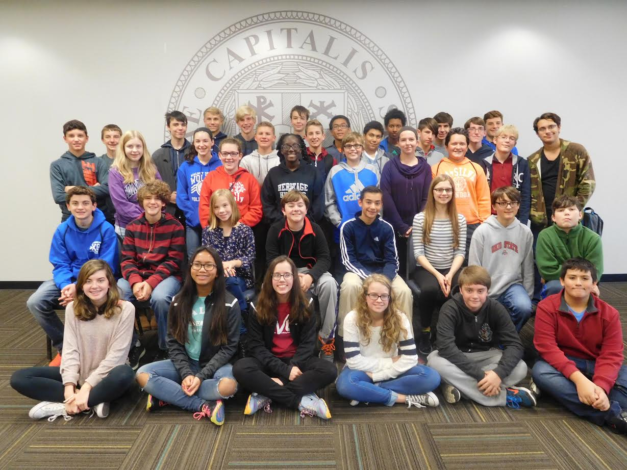 Forty students from Blendon, Genoa, Heritage and Walnut Springs Middle Schools sit in front the Capital University Seal