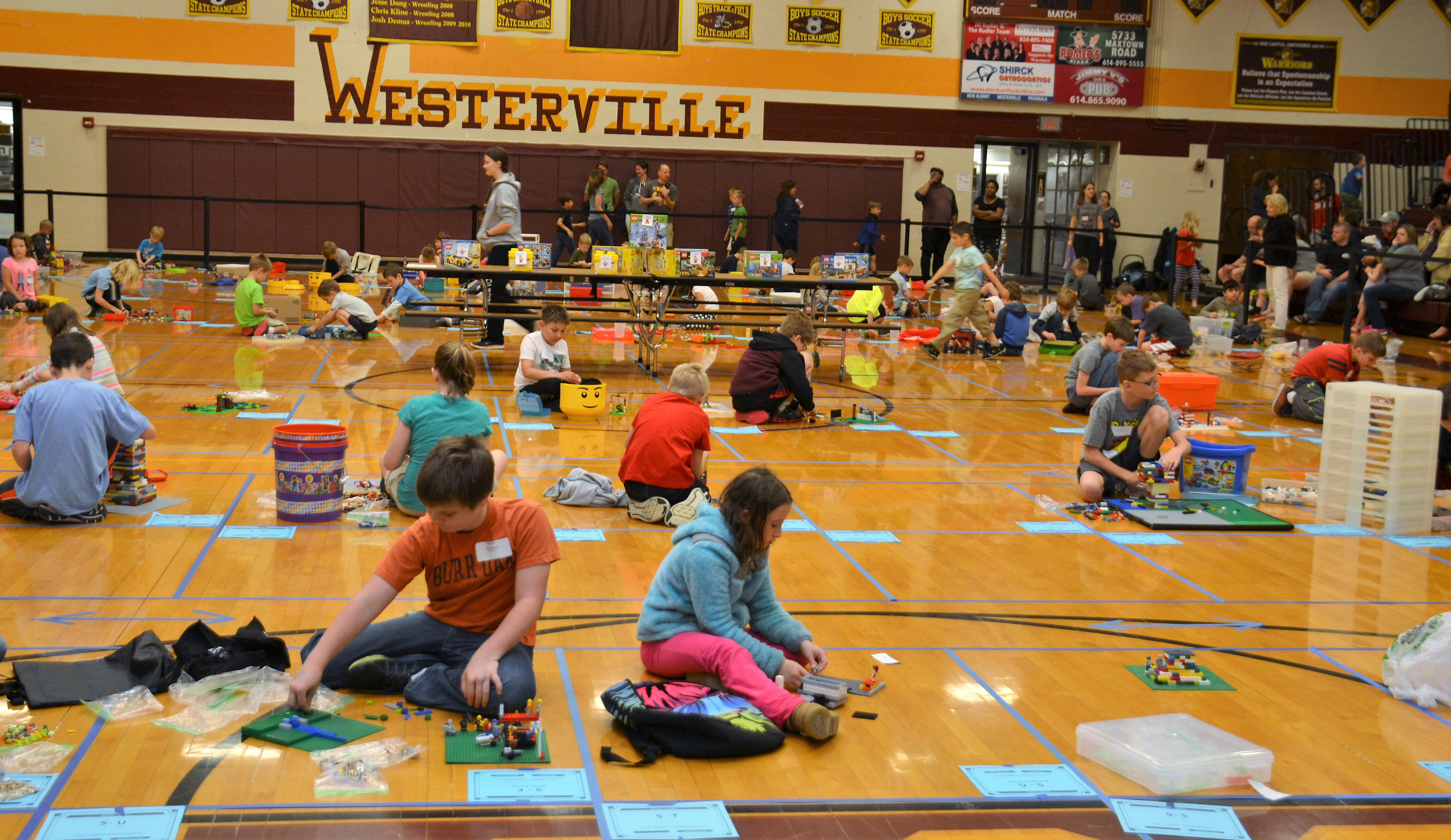 Dozens of students building with Legos on the gym floor at WNHS.
