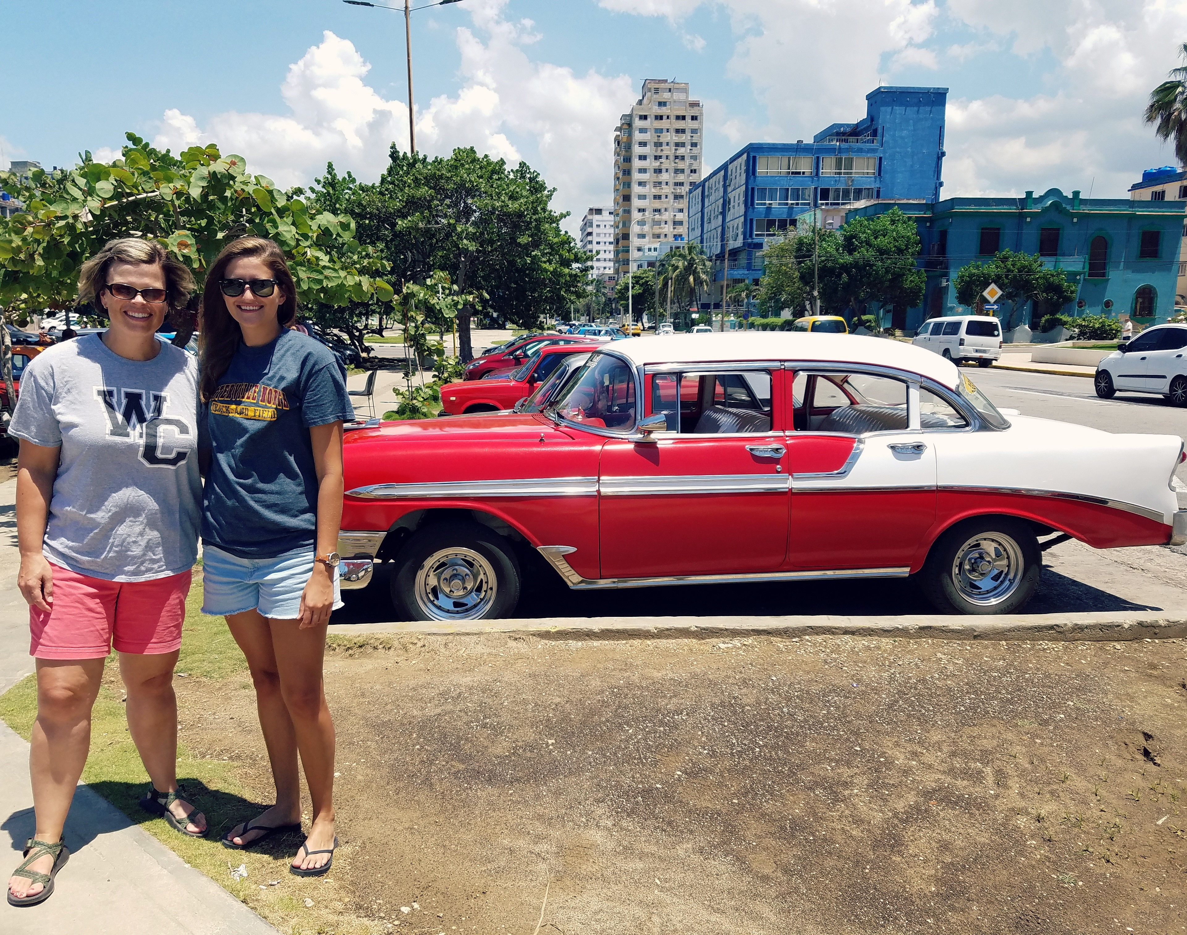 Spanish teachers pose in front of a vintage 1957 Chevy, parked in Havana.