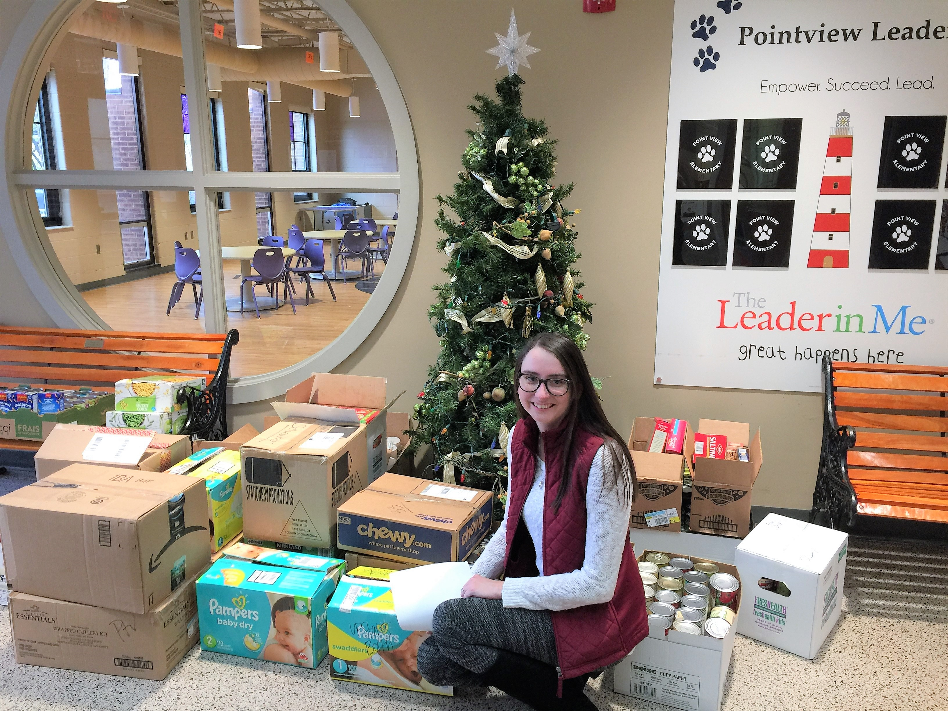 Elyson Barto in front of donations to Pointview's Caring & Sharing drive