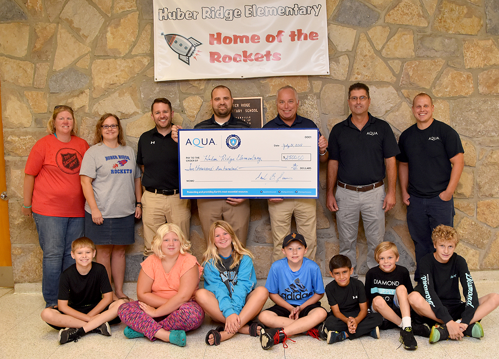 Tyson Hilkert accepts a check from Aqua Ohio representatives