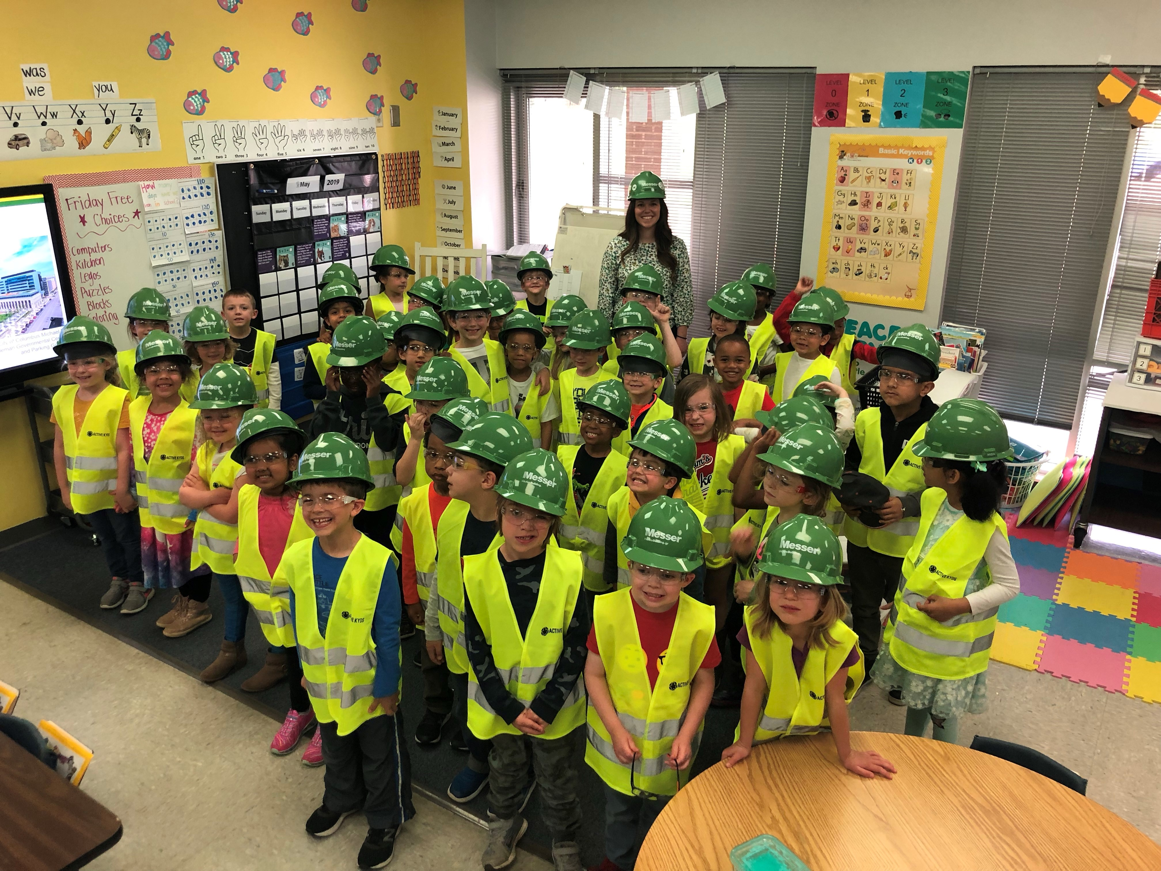 Kindergarten students with hard hats, goggles and vests