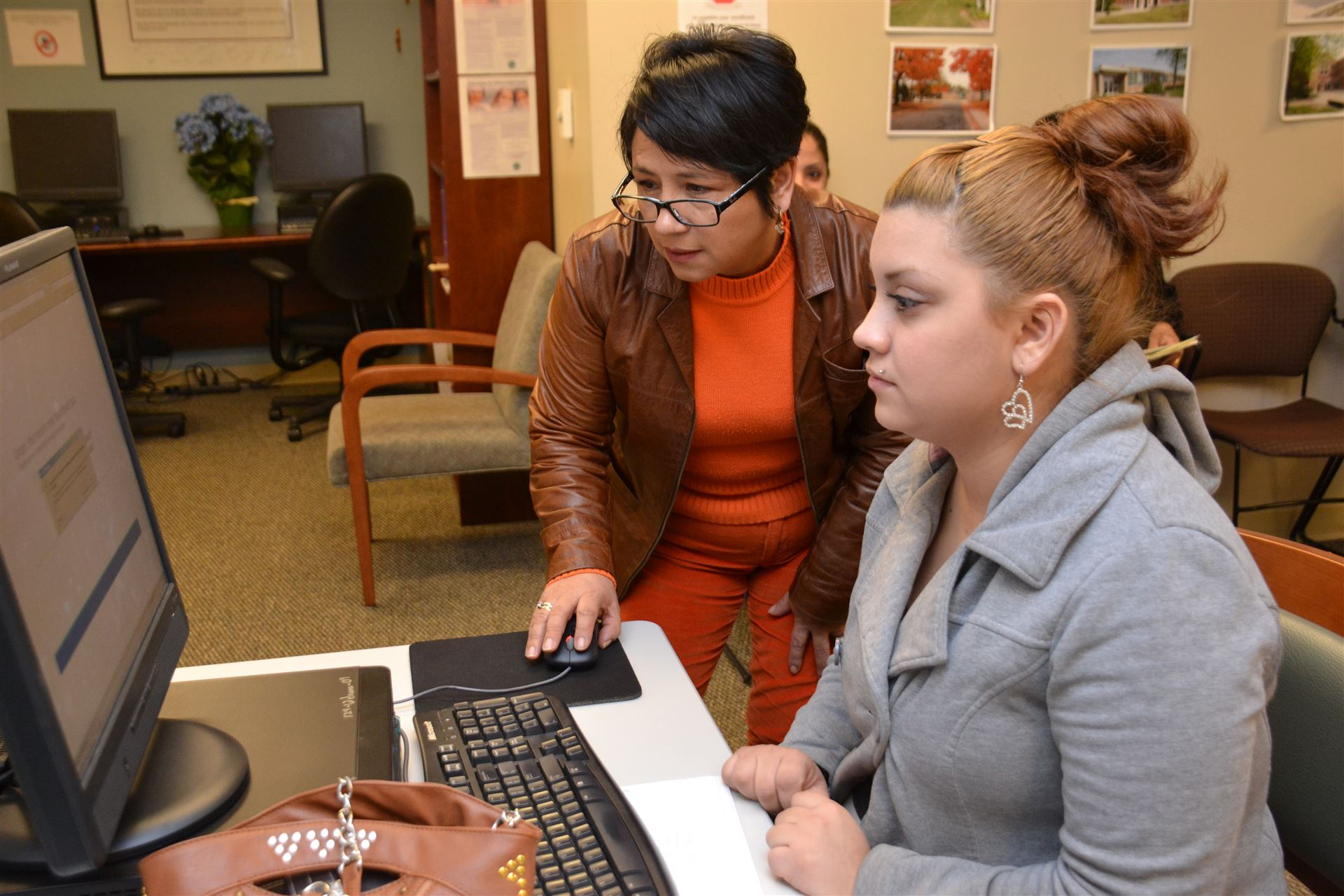 Marlene Torrez-Graham helps a Spanish-speaking parent register their children for kindergarten.