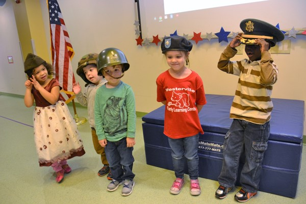 Preschoolers try military headgear during Veteran's Day program.