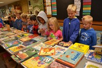 First grade students at Mark Twain Elementary School ponder their choice of books that are placed on a very large table