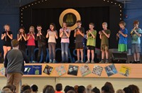 Students on stage performing songs.