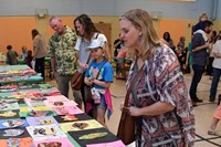 Families looking at displayed artwork.