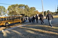 Students board a school bus during the district's reunification drill on October 16.