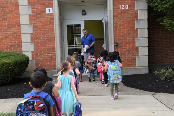 Kindergarten students entering school building